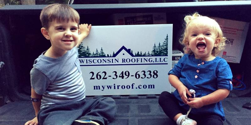 Kids Posing with a Wisconsin Roofing, LLC Yard Sign